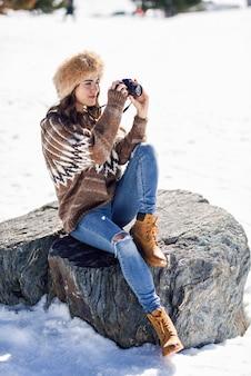 Jovem mulher tirando fotografias nas montanhas nevadas