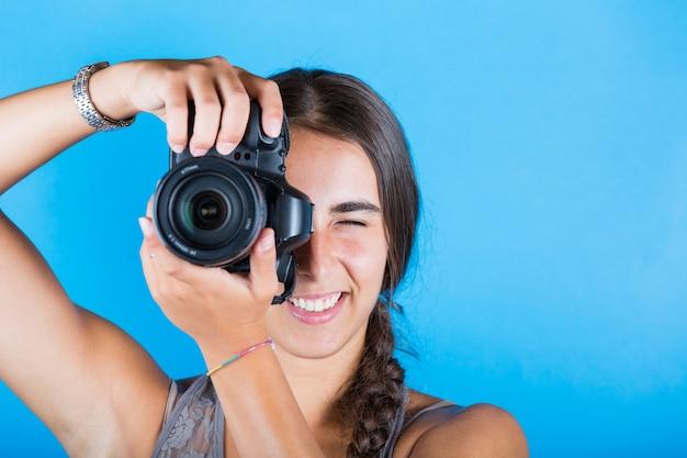Jovem mulher tirando fotos com uma câmera profissional
