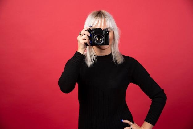 Jovem mulher tirando fotos com uma câmera sobre um fundo vermelho. foto de alta qualidade