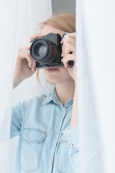 Jovem mulher tirando fotos secretamente pela janela