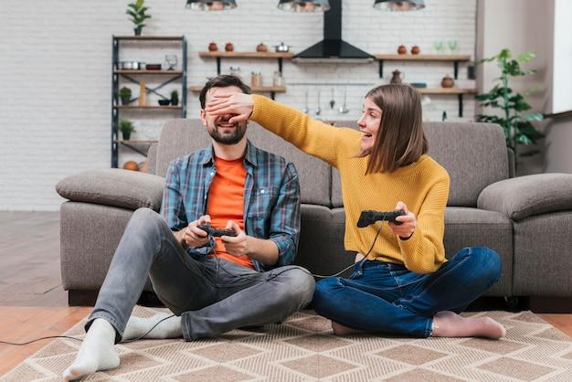 Jovem mulher tirando sarro de seu marido jogando videogame em casa