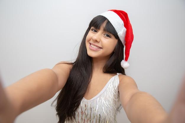 Jovem mulher tirando selfie com chapéu de papai noel