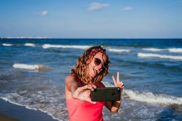 Jovem mulher tirando uma foto com o celular na praia