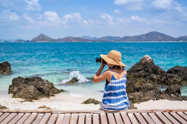 Jovem, mulher tirar uma foto na praia tropical