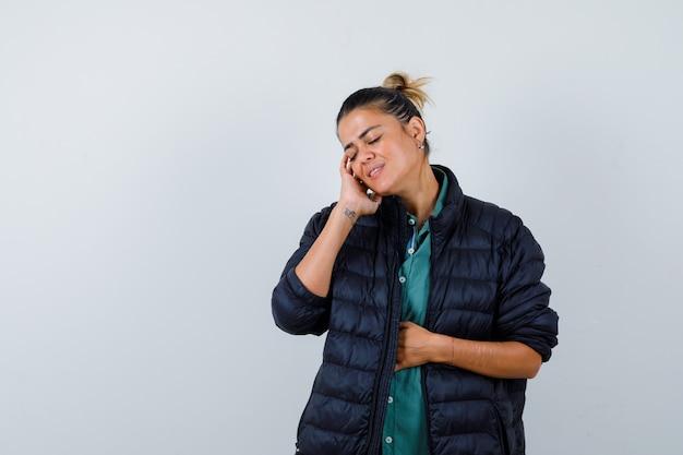 Jovem mulher tocando a bochecha com a mão na camisa, jaqueta de baiacu e parecendo delicada. vista frontal.