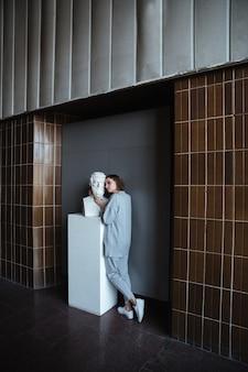 Jovem mulher tocando busto de mármore