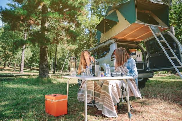 Jovem mulher tocando gaita sentado no acampamento com sua amiga. tempo de lazer e conceito de diversão.