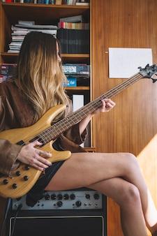 Jovem, mulher, tocando, guitarra, amplificador