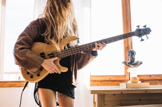 Jovem mulher tocando guitarra elétrica perto da janela
