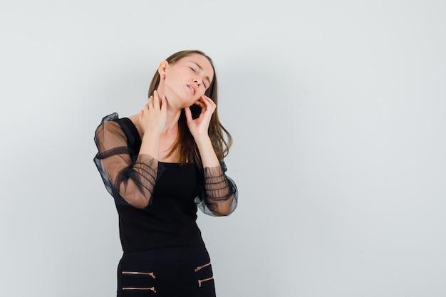 Jovem mulher tocando seu pescoço com uma blusa preta e parecendo dolorida. vista frontal. espaço para texto