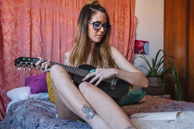 Jovem, mulher, tocando, ukulele, cama