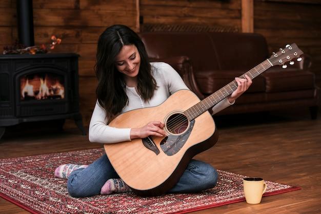 Jovem mulher tocando violão em casa