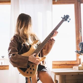 Jovem, mulher, tocando, violão, perto, janela Foto gratuita