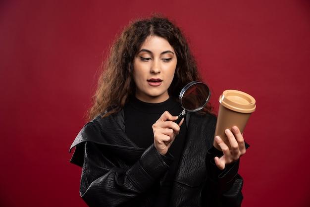 Jovem mulher toda vestida de preto, segurando uma xícara com lupa.