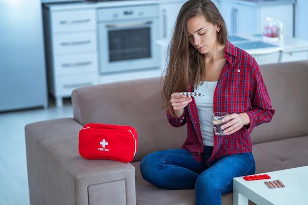 Jovem mulher toma remédio em casa. kit de primeiros socorros com comprimidos de doenças e dores