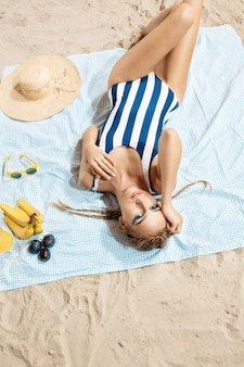 Jovem mulher tomando banho de sol com roupa de banho listrada