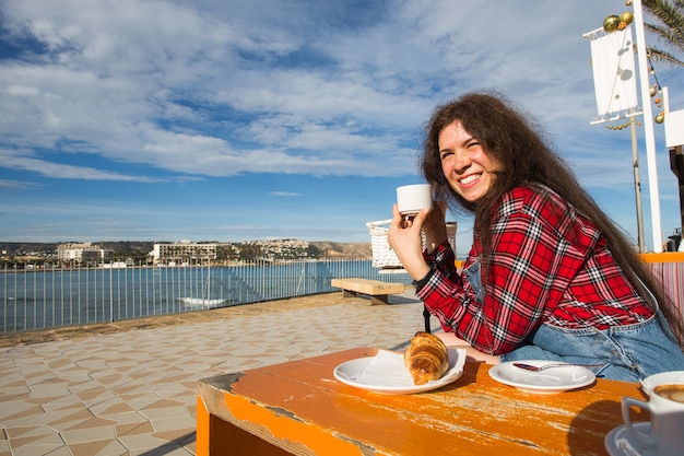 Jovem mulher tomando café da manhã com croissant e café no café na rua em frente ao mar.