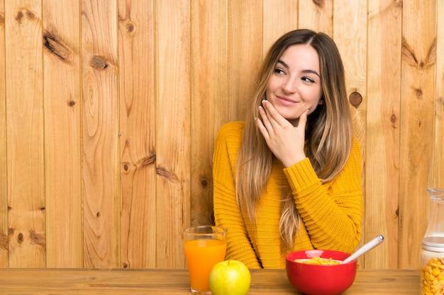 Jovem mulher tomando café da manhã em uma cozinha pensando uma idéia