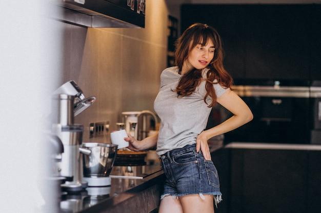 Jovem mulher tomando café da manhã na cozinha