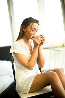 Jovem mulher tomando café da manhã no quarto