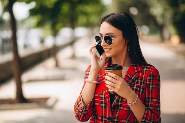 Jovem mulher tomando café e falando ao telefone
