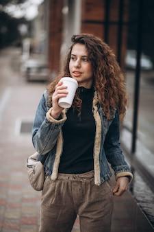 Jovem mulher tomando café e usando o telefone