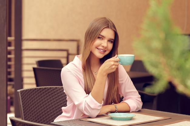 Jovem mulher tomando café em um café ao ar livre