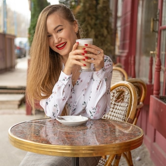 Jovem mulher tomando café em um café de rua parisiense