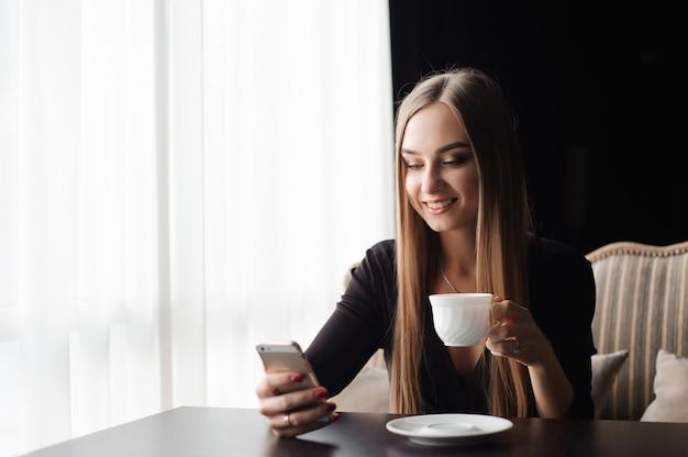 Jovem mulher tomando café em um café e usando um telefone celular.