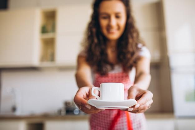 Jovem mulher tomando café na cozinha pela manhã