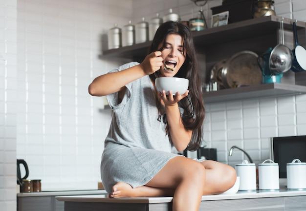 Jovem mulher tomando café na cozinha