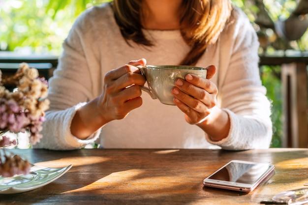 Jovem mulher tomando café na mesa de madeira com telefone inteligente no café durante o tempo livre.