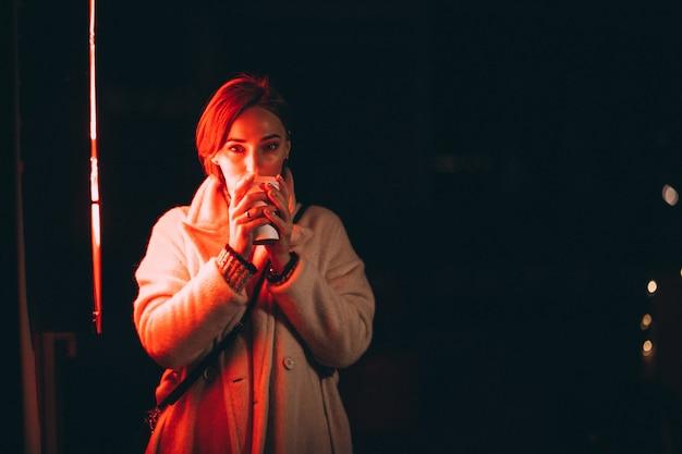 Jovem mulher tomando café na rua à noite