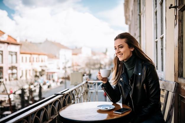 Jovem mulher tomando café na varanda.