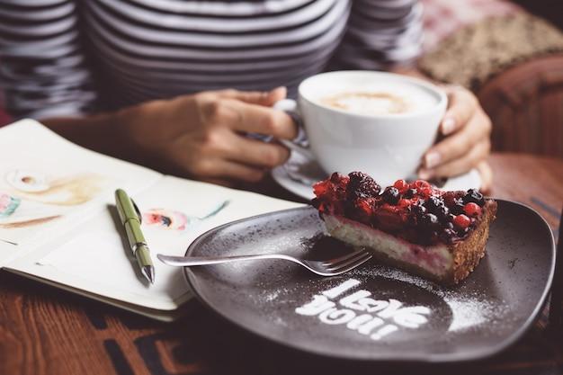 Jovem mulher tomando café no café urbano