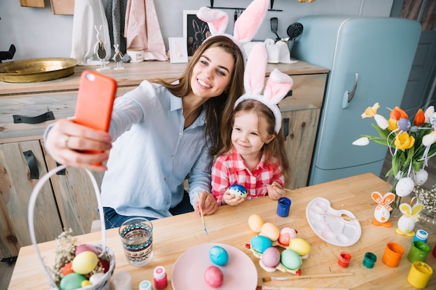 Jovem mulher tomando selfie com a filha perto de ovos de páscoa