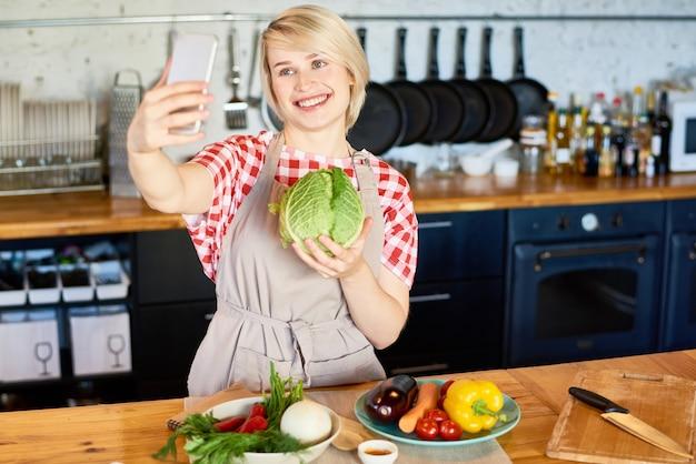 Jovem mulher tomando selfie na cozinha