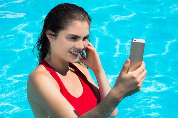 Jovem mulher tomando selfie na piscina.