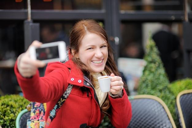 Jovem mulher tomando um auto-retrato (selfie) com telefone inteligente em um café de rua parisiense