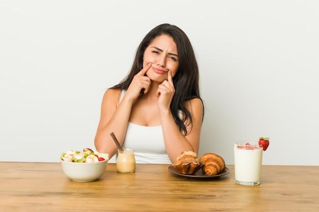 Jovem mulher tomando um café da manhã duvidando entre duas opções.