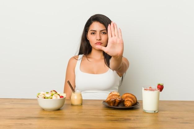 Jovem mulher tomando um café da manhã em pé com a mão estendida, mostrando o sinal de stop, impedindo-o.