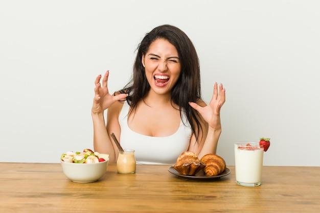 Jovem mulher tomando um café da manhã gritando de raiva.