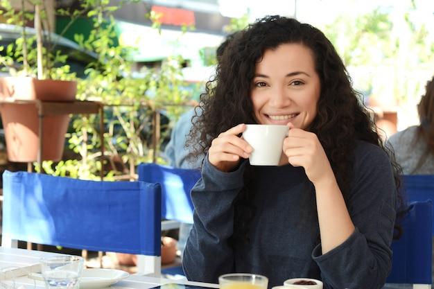 Jovem mulher tomando um café