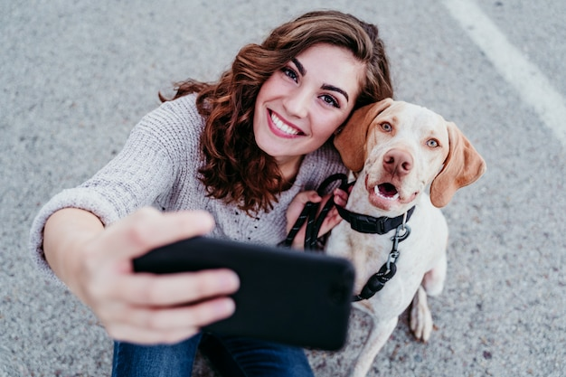 Jovem mulher tomando uma selfie com telefone celular com seu cachorro na rua