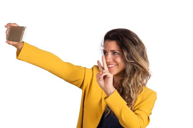 Jovem mulher tomando uma selfie com telefone.