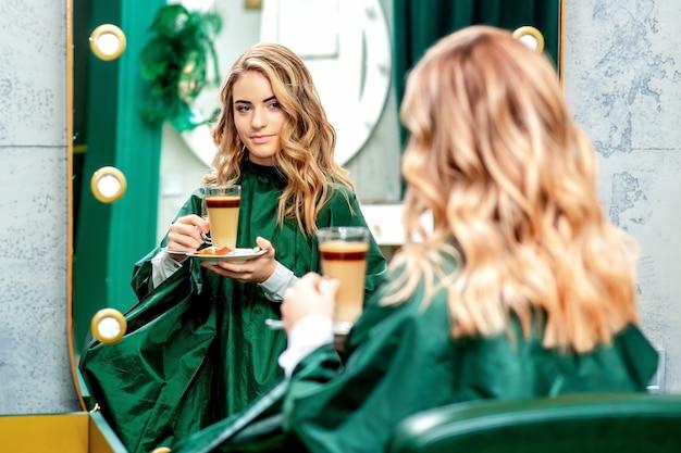 Jovem mulher tomando uma xícara de café com leite, olhando no espelho no salão de beleza.