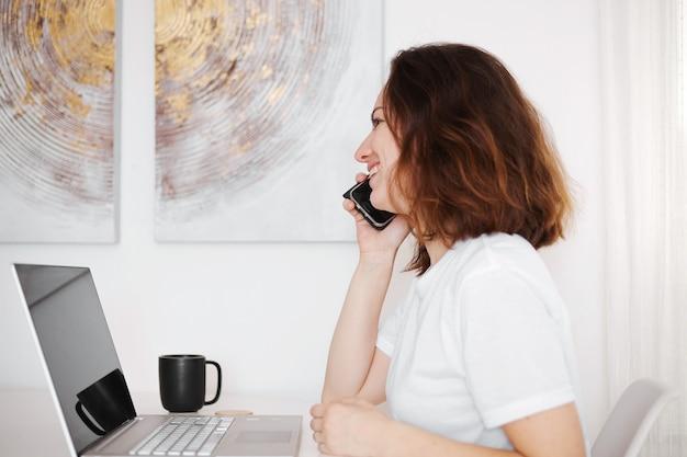 Jovem mulher trabalhando com computador em casa e falando no smartphone. garota alegre e positiva trabalha em um escritório em casa. trabalho com laptop, interior branco e moderno.