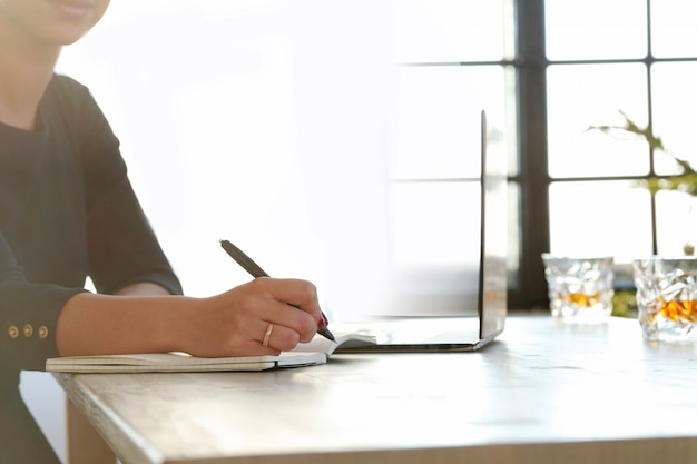Jovem mulher trabalhando com laptop e agenda