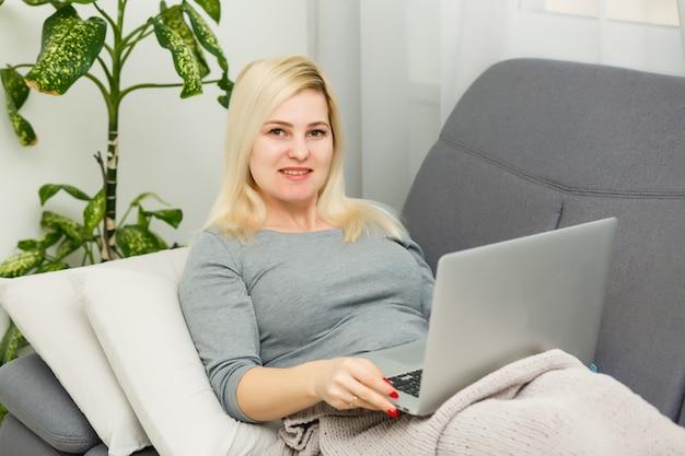 Jovem mulher trabalhando em um laptop em casa. menina sentada em uma cama com um computador. quarentena, conceito de ficar em casa. coronavírus (covid-19