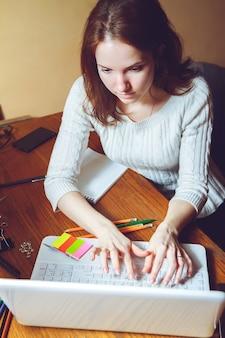 Jovem mulher trabalhando em um laptop sentada no local de trabalho
